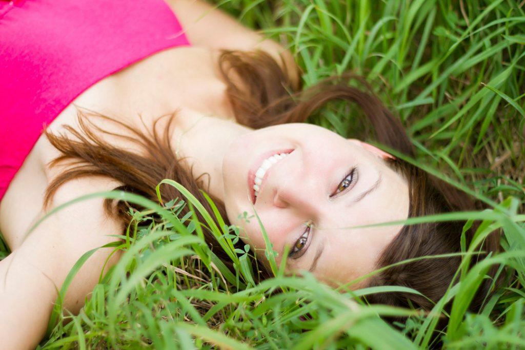 Happy woman good skin lying in grass