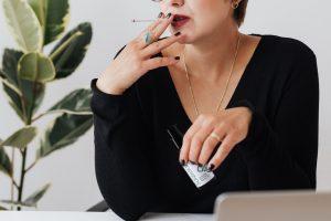Woman smoking holding Soji Health oil product